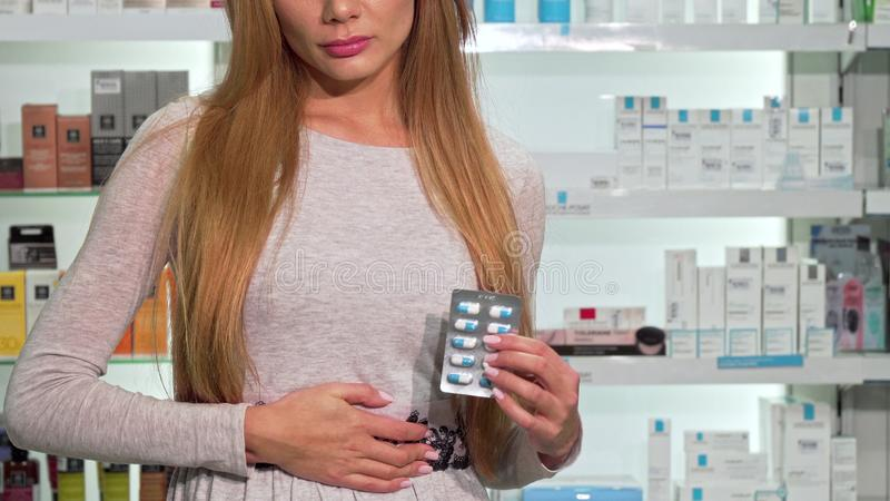 Woman with stomach ache buying prescription medication at the drugstore. Cropped shot of a female having abdominal pain holding blister of pills at pharmacy royalty free stock image