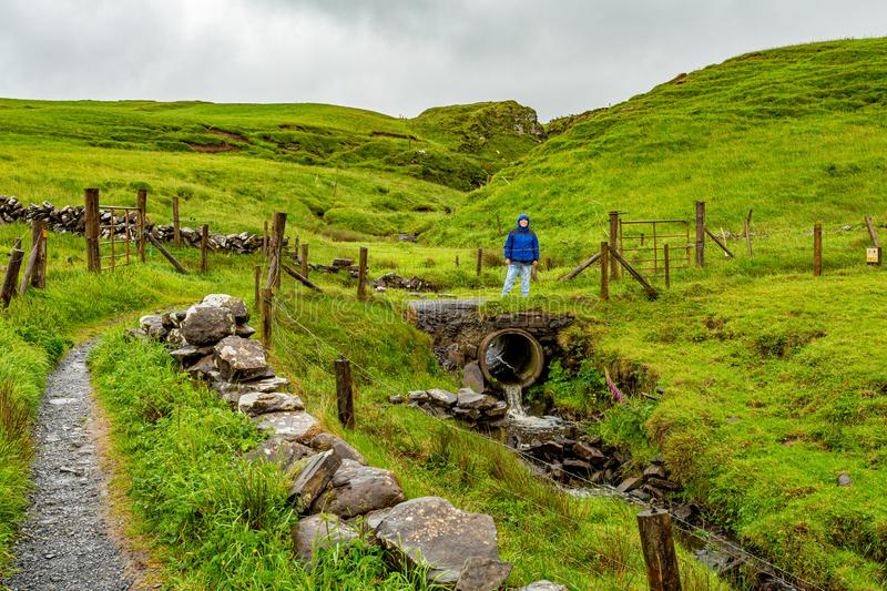 Woman on a stone bridge on the coastal walk route from Doolin to the Cliffs of Moher. Geosites and geopark, Wild Atlantic Way, spring rainy day in the stock image