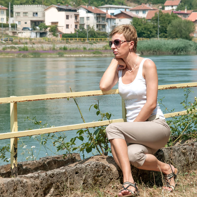 Woman on the Stone near the river royalty free stock images