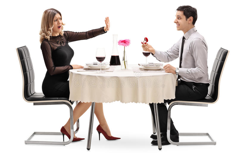 Woman stopping her boyfriend from proposing. Woman trying to stop her boyfriend from proposing seated on a romantic date isolated on white background royalty free stock photography