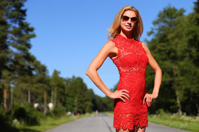 Woman stops a passing car. On a country road stock photo