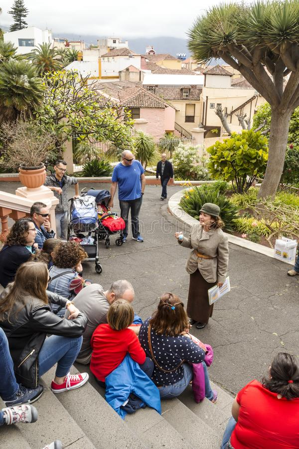 Woman storyteller. Surrounded by children in the victoria gardens of the orotava. It is an editorial image in verticao on a cloudy day royalty free stock images