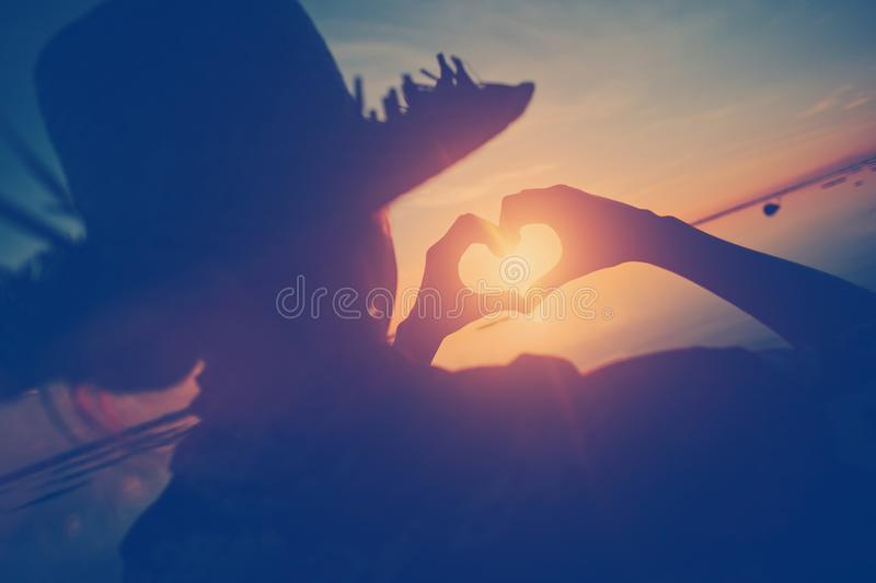 Woman In Straw Hat Making Heart Symbol With Her Hands At Sunset