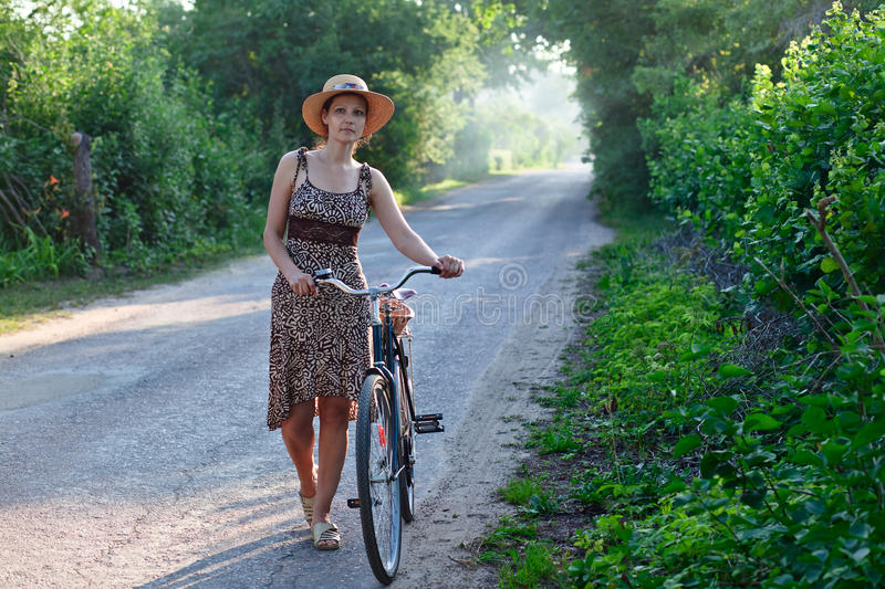 Woman in straw hat. The woman of middle age in straw hat with bicycle stock photography