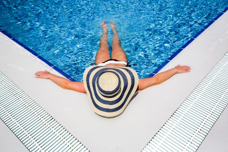 Woman in straw hat relaxing swimming pool royalty free stock images