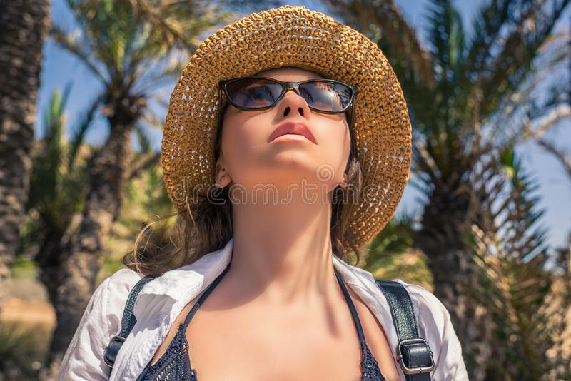Woman in the straw hat and in sunglasses looking on the sky in the palm trees forest. Seychelles islands. royalty free stock photos