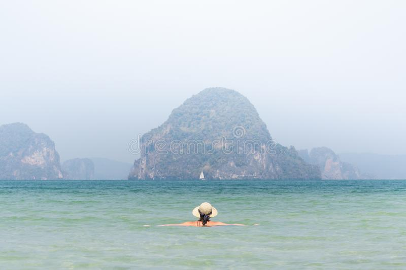Woman in straw hat swiming in the sea in Krabi Railey beach overlooking the harbour and mountains, Thailand stock photo