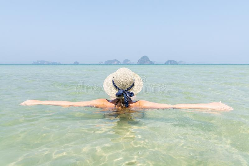 Woman in straw hat swiming in the sea in Krabi Railey beach overlooking the harbour and mountains, Thailand stock photography