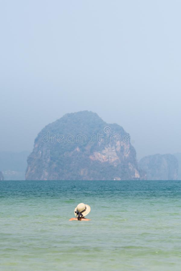 Woman in straw hat swiming in the sea in Krabi Railey beach overlooking the harbour and mountains, Thailand royalty free stock photography