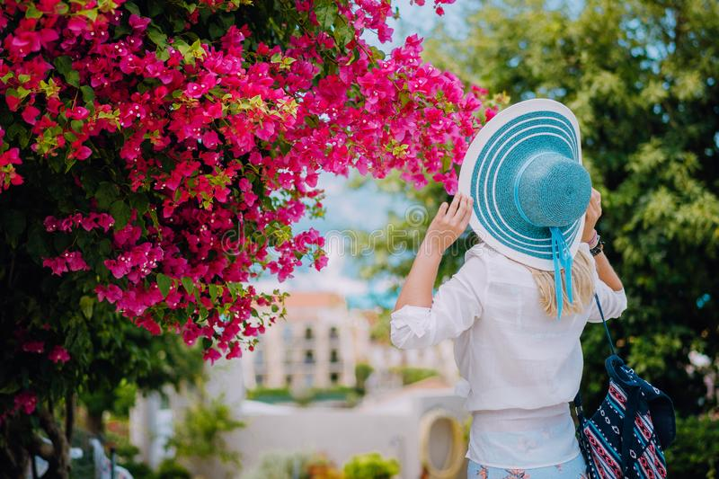Woman with straw hat and vivid flowers. Amazing summer time on mediterranean sea. Romantic Traveling vacation concept royalty free stock image