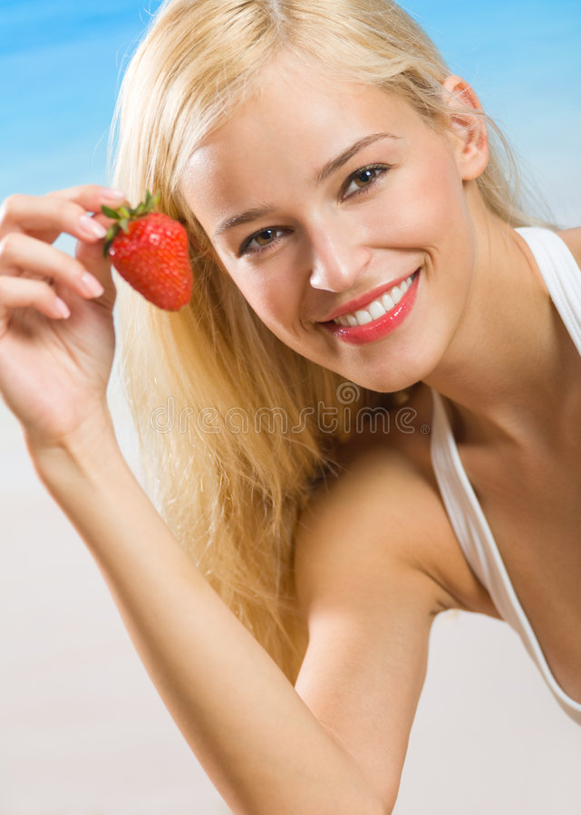 Woman with strawberry on beach. Young woman with strawberry on beach stock photo