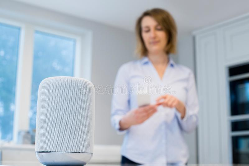 Woman Streaming Music Wirelessly From Mobile Phone To Speaker royalty free stock photos