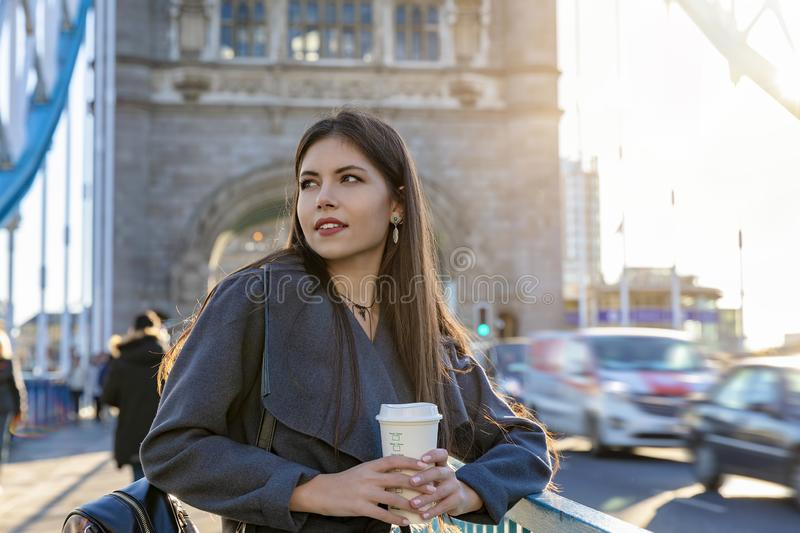 Woman on a street with a coffee in her hand, Tower Bridge, London, UK. Attractive urban city woman outdoors on a street with a coffee in her hand, Tower Bridge royalty free stock images