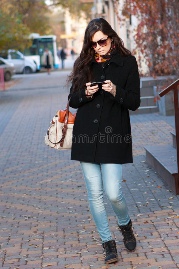It woman on street with phone. It woman on street with the phone royalty free stock photography