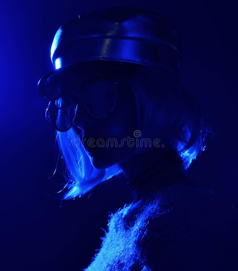 Woman in street style fashion winter concept wearing gold hat cap and round sunglasses in pink neon light royalty free stock images