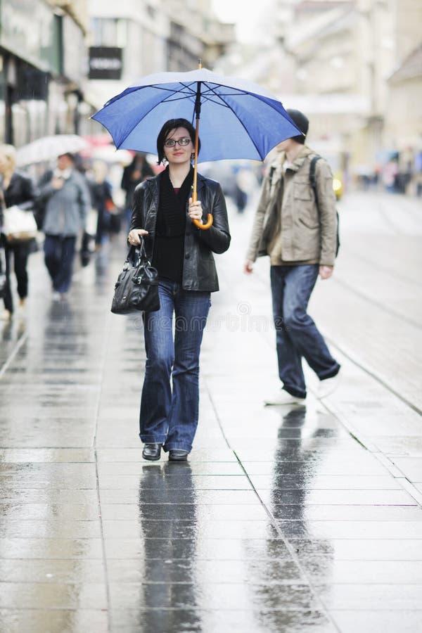 Woman on street with umbrella stock image