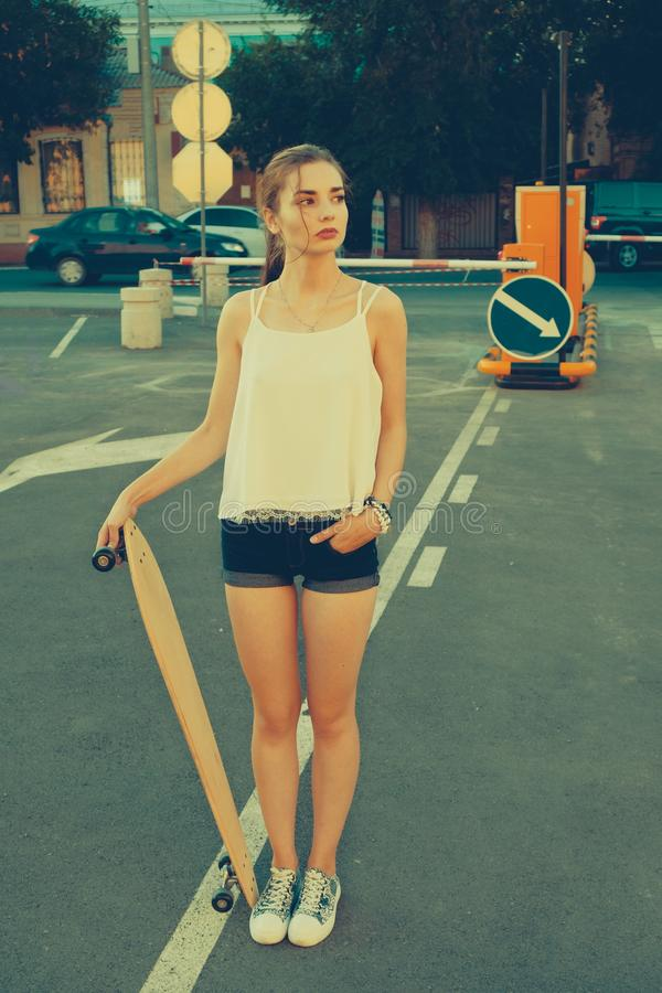 Woman in street vintage fashion wear standing on parking lot in front of road signs and looking away while holding. Longboard, copyspace on the right side of royalty free stock photo