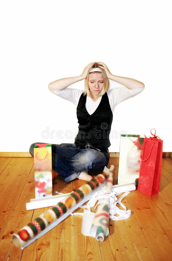 Woman with stress on christmas. A young woman is wrapping christmas gifts and is stressed out stock image