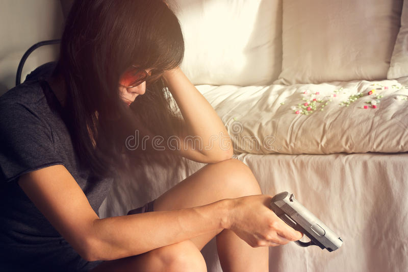Woman stress and depressed of her sickness, she decided to kill herself with a gun in hand. Woman stress and depressed of her sickness, she decided to kill royalty free stock images