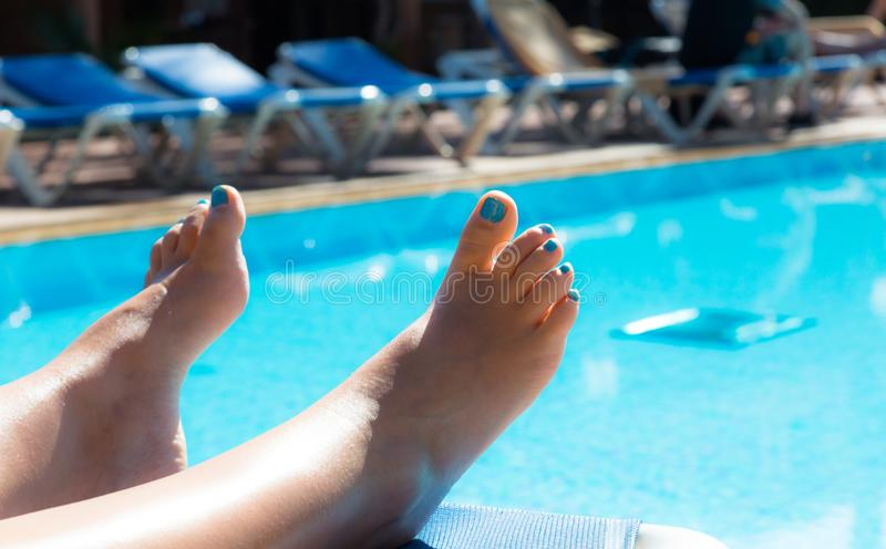 Woman stretched legs at swimming pool with clear turquoise water. Woman stretched legs, with nails painted in turquoise colour, at swimming pool with clear royalty free stock photo