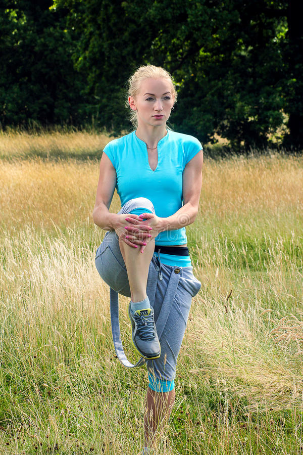 Woman stretches her legs in the park. Fit blonde woman stretching her lower body stock photo