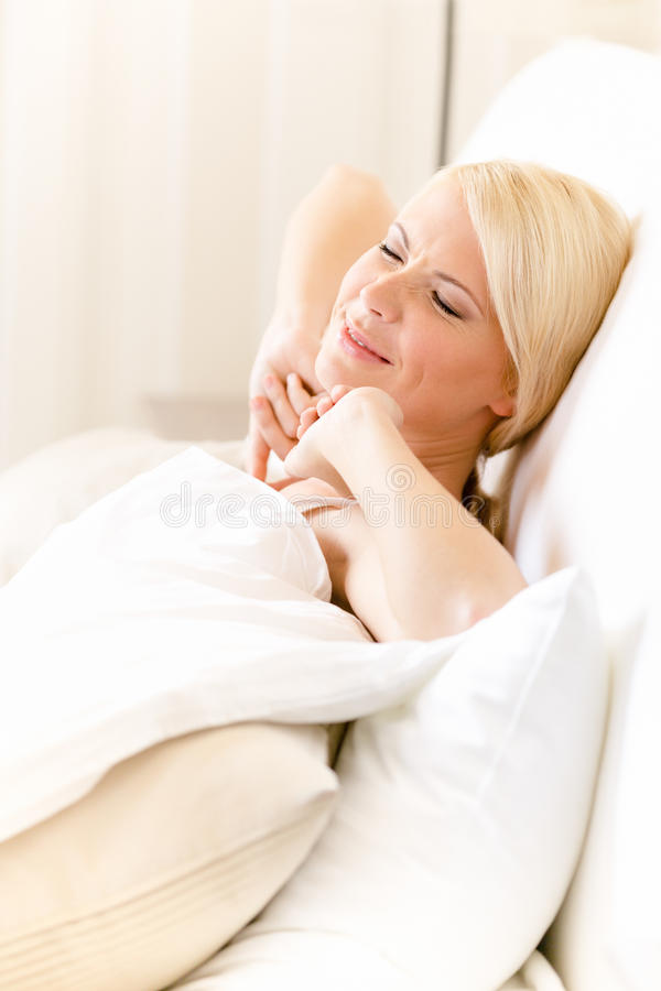 Download Woman Stretches Herself Lying In Bed Stock Image - Image: 30457979