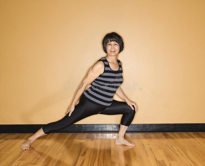 Woman Stretches Leg in Yoga Pose royalty free stock image