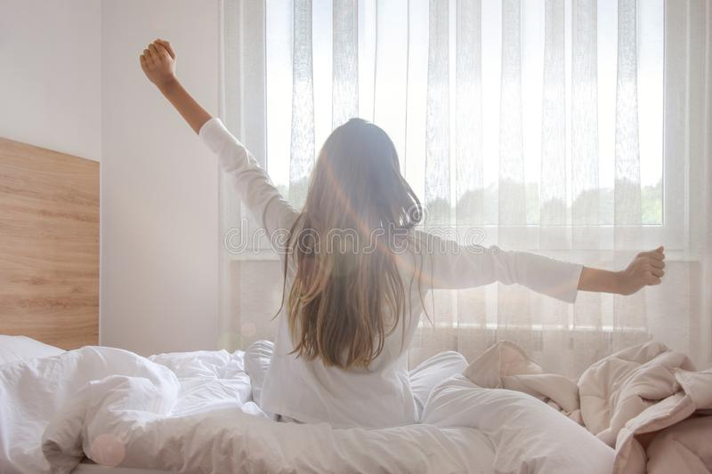 Young woman waking up in her bedroom, sitting on the bed stretching arms by the window royalty free stock images