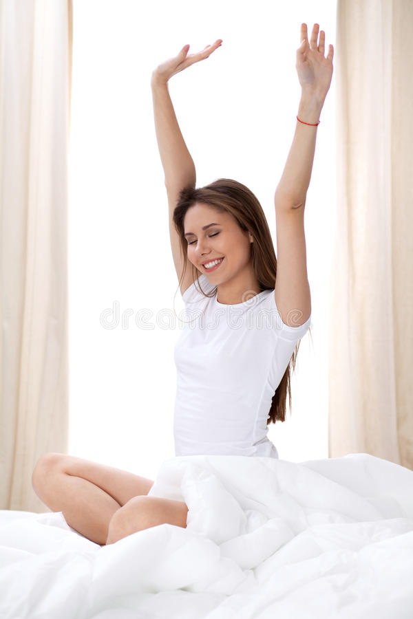 Woman stretching in bed after wake up, entering a day happy and relaxed after good night sleep. Sweet dreams, good stock images