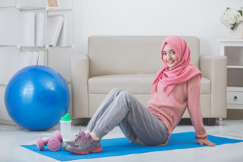 Woman stretching while doing exercise at home stock images