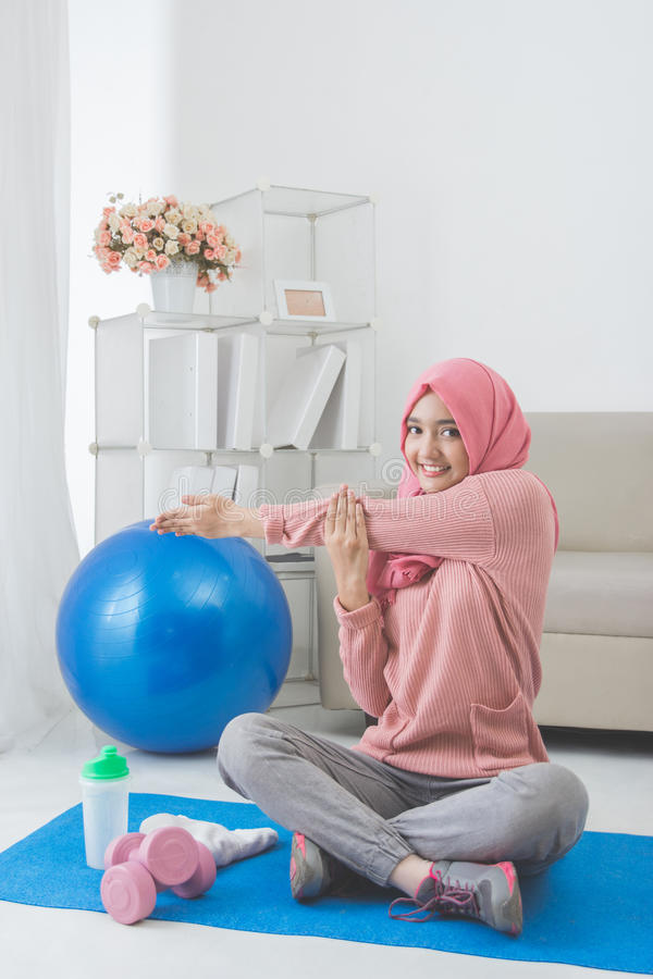 Woman stretching while doing exercise at home royalty free stock images