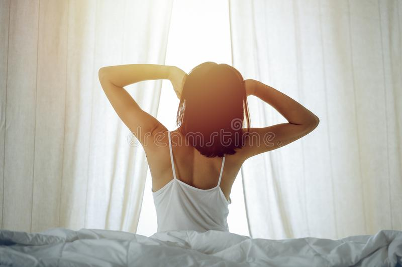 Woman stretching hands in bed after wake up, sun flare . Brunette entering a day happy and relaxed after good night. Sleep and back view. Concept of a new day royalty free stock photography