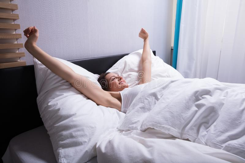 Woman Stretching Her Hands On Bed royalty free stock photo