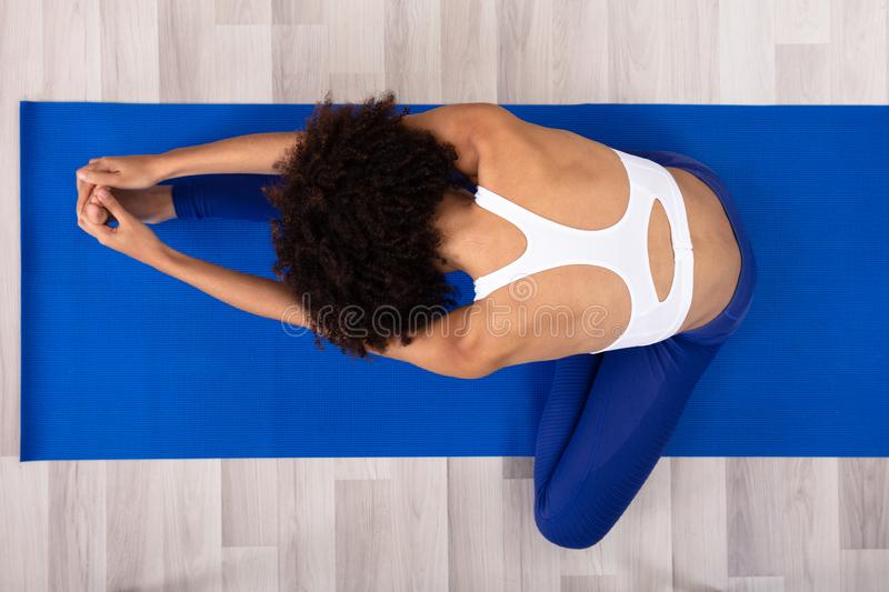 Woman Stretching Her Leg On Exercise Mat royalty free stock photos