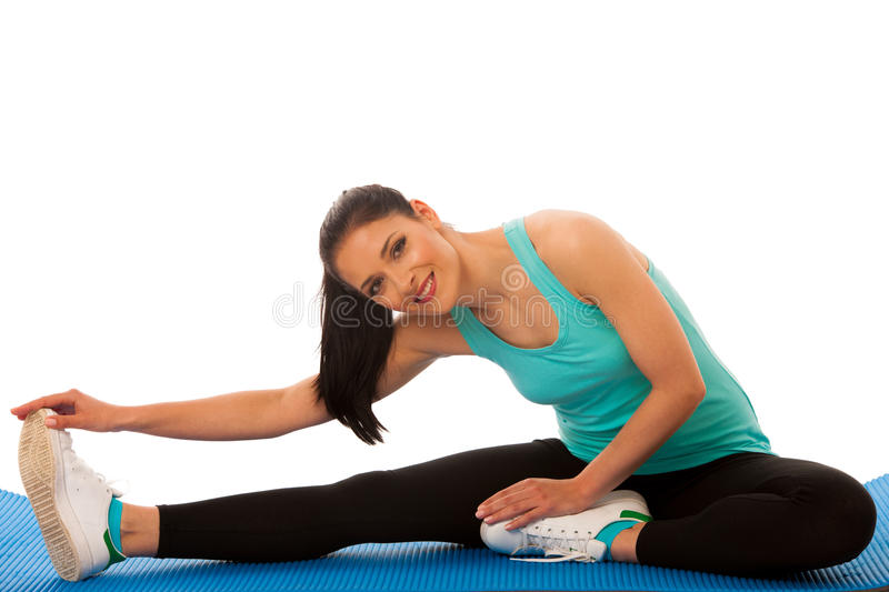 woman stretching legs on blue mat, isolated over white background royalty free stock image