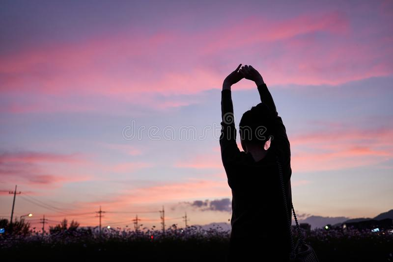 Woman stretching and looking at the sunset sky of Jechun, South Korea royalty free stock photos