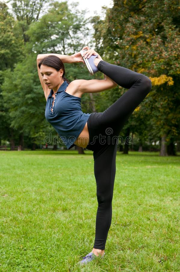 Woman stretching muscles before. Young beautiful flexible woman stretching muscles before jogging - outdoors in nature stock photography