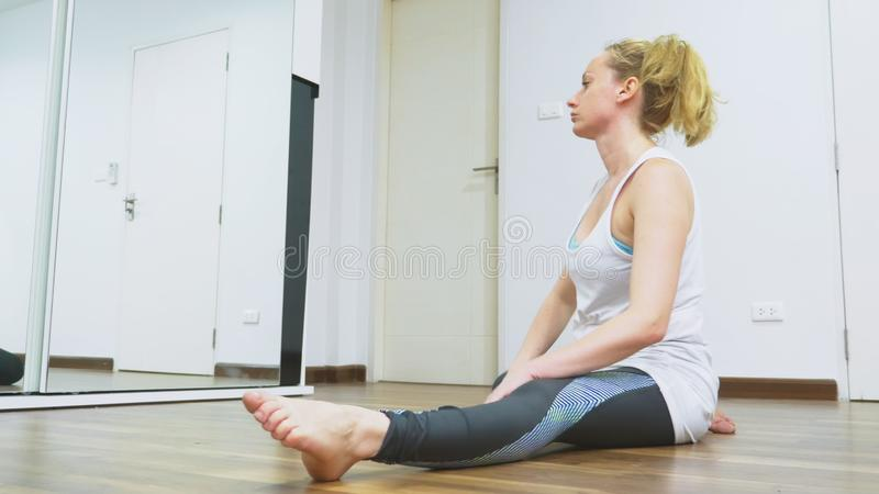 Woman stretching near mirror at her apartment. The concept of a healthy lifestyle, not a professional sport. stock photo