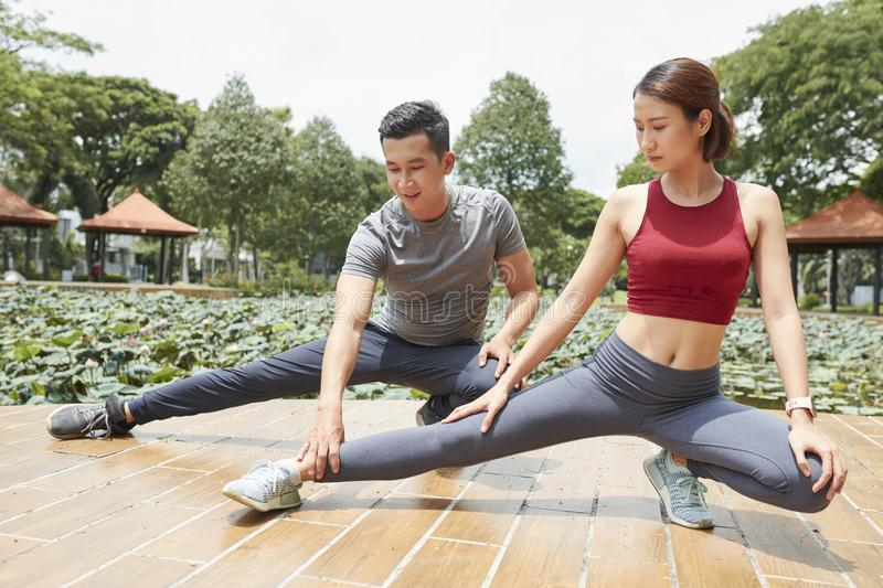 Woman stretching with trainer stock photos