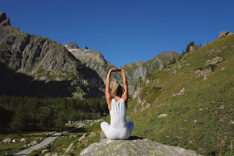 Woman stretching and yoga. Mountain backgroud stock image