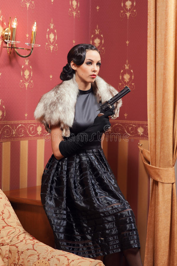 The woman in strict clothes in a retro style. The woman in strict clothes in a retro style the 30-th of years. The girl costs in a corner of the room and sat royalty free stock images