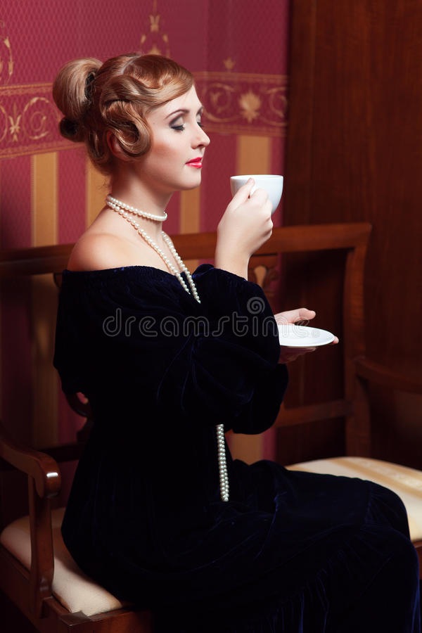The woman in strict clothes in a retro style. The woman in strict clothes in a retro style the 30-th of years. The girl sits on a shop with a cup of tea and a royalty free stock photos