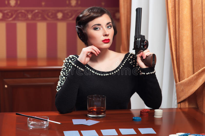 The woman in strict clothes in a retro style. The woman in strict clothes in a retro style the 30-th of years. The girl sits at a table the right hand at the stock photo