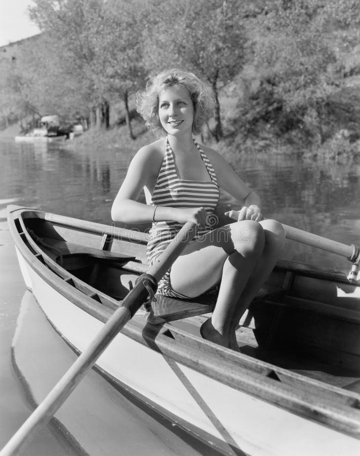 Woman in a striped bathing suit rowing stock photo