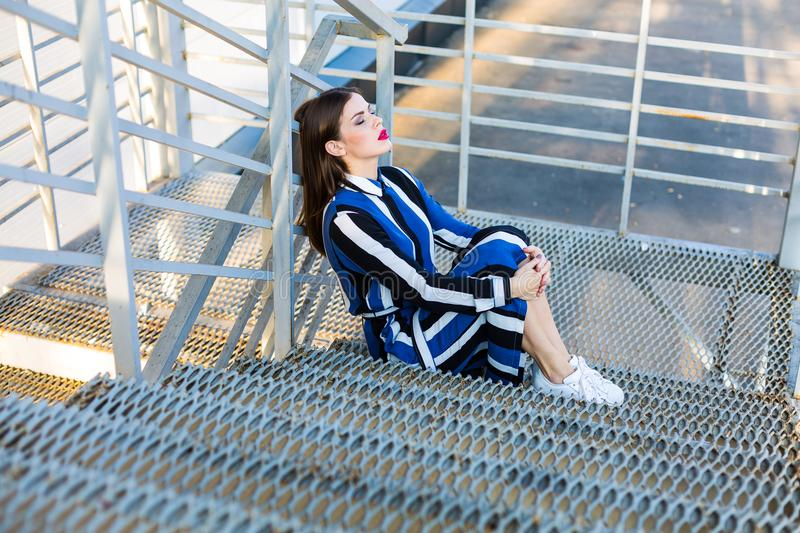 Woman sitting on a metal stairs stock photo