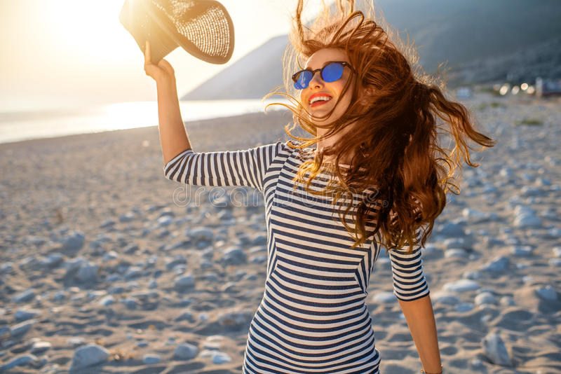 Woman in stripped dress with a hat on the beach royalty free stock photos