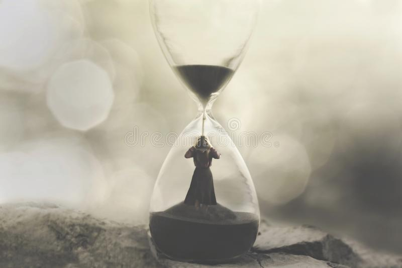 Woman stuck in an hourglass, concept of being prisoners of time passing royalty free stock photos
