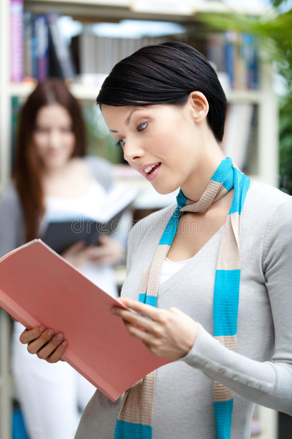 Woman student at the library against bookshelves royalty free stock photo