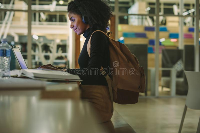 Woman student at library using laptop stock image