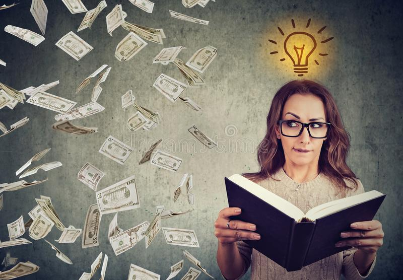 Student reading a book has a bright idea how to earn money stock photography